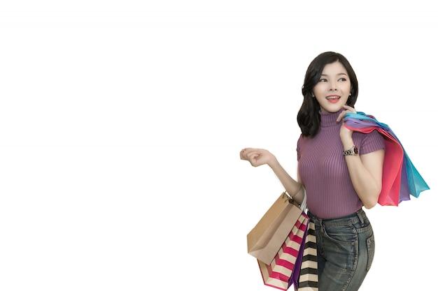 美しい女性は、クレジットカードを使用してショッピングモールで買い物します。眼鏡をかけていると買い物袋のファッションを保持している女性