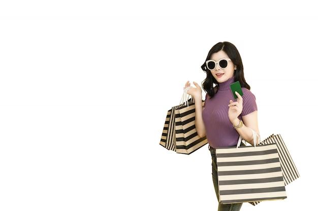 Красивая женщина ходит по магазинам в торговом центре используя кредитную карточку. женщина нося стекла и держа моду хозяйственной сумки в универмаге.
