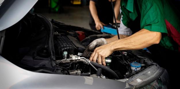 自動車整備士の交換オイルマシン。男はモーターオイルを交換しています。エンジンオイルを交換します。自動車オイルの交換。自動車のメンテナンスを確認します。輸送修理サービスセンター