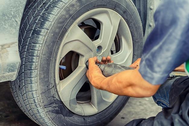Человек с помощью автомеханика заблокируйте ветровое колесо. проверять ваши шины и тормоза для автомобиля. автомеханик готовимся к работе.