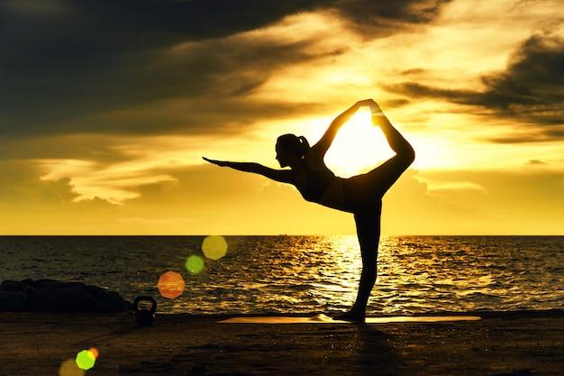 アブストラクト。シルエットヨガ。海でヨガを練習する若い女性の肖像画。海でリラックス。瞑想