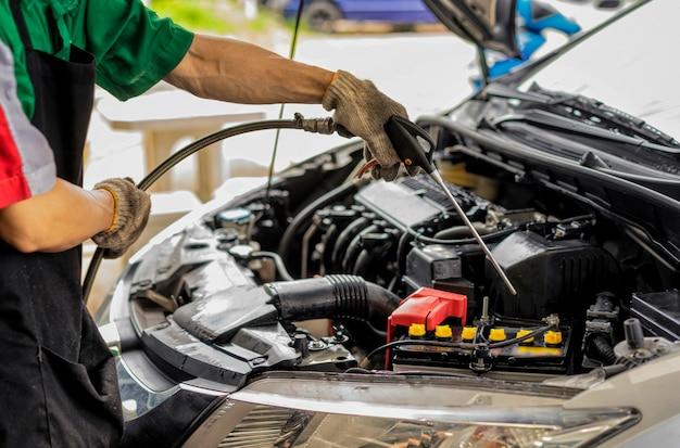車のエンジンルームを掃除します。車のエンジンルームを洗います。洗車機。車のメンテナンスの概念。