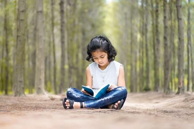アジアの子供たちは、庭園で読書をリラックスしています。教育と人々のコンセプト。学校への戻り