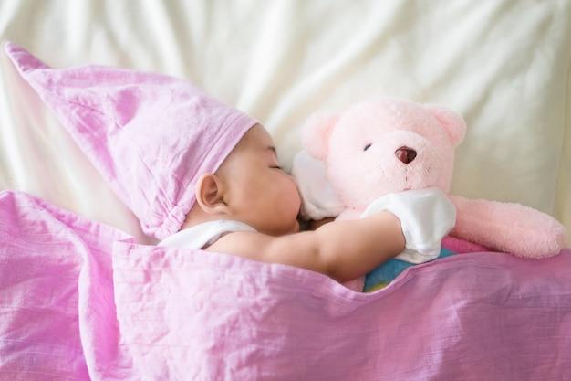 Милый ребенок лежит на кровати. новорожденный спит с плюшевым мишкой. два месяца