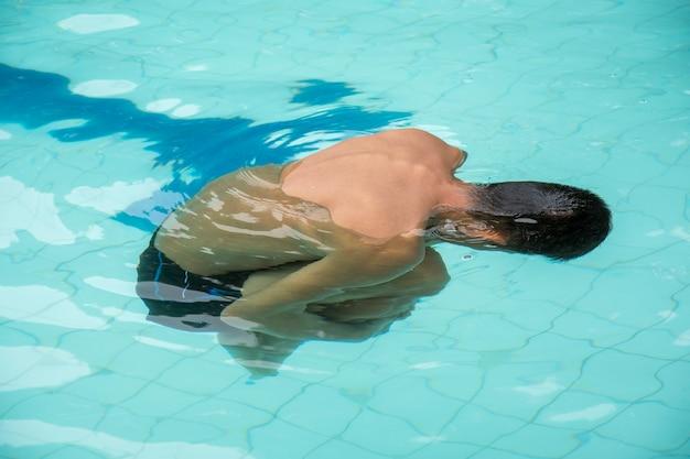 プールに浮かぶ若者