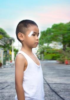 Мальчик-мальчик с потрескавшейся головой и врачом, используя марлю, закрывающую рану