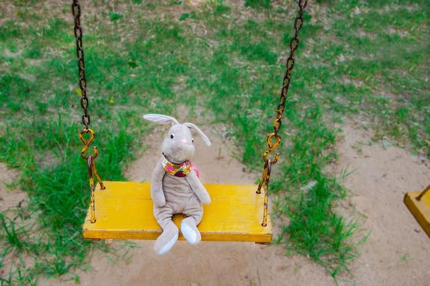 ブランコに乗るウサギの人形。
