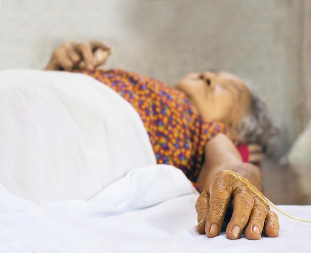 生理食塩水の点滴で病院の高齢者の患者を手します。