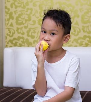 小さな男の子は、学校から帰った後、スナックのためにドリアンを食べることを楽しむ