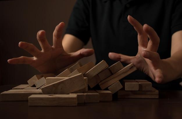 手の男の背景によって落ちて木製のスタックブロックタワーとビジネスのアイデアの概念を混乱させる