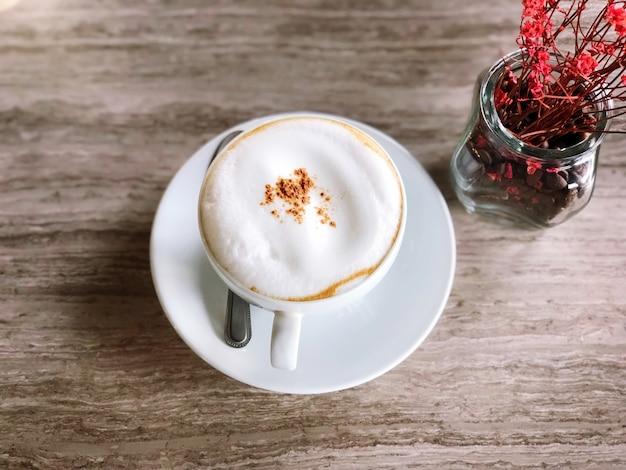 大理石のテーブルと花の上に白いカップでホットコーヒーとコーヒーショップのトップビュー