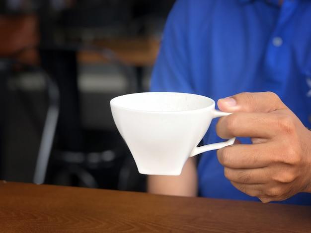 アジア人男性がコーヒーショップでより多くのコーヒーを飲むためにグラスをキャッチ