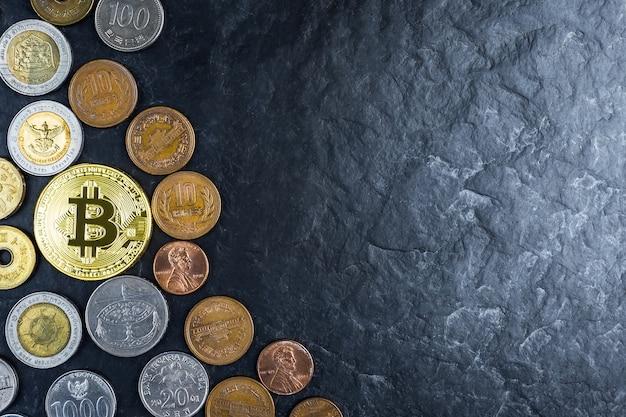 国際的なお金のコイン、黒の石テーブルの背景とゴールデンビットコイン