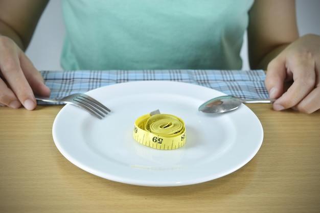 Концепция диеты. руки с набором вилки и рулеткой на пластине.