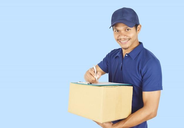 Молодая доставка держа коробку и что-то писать в буфер обмена.