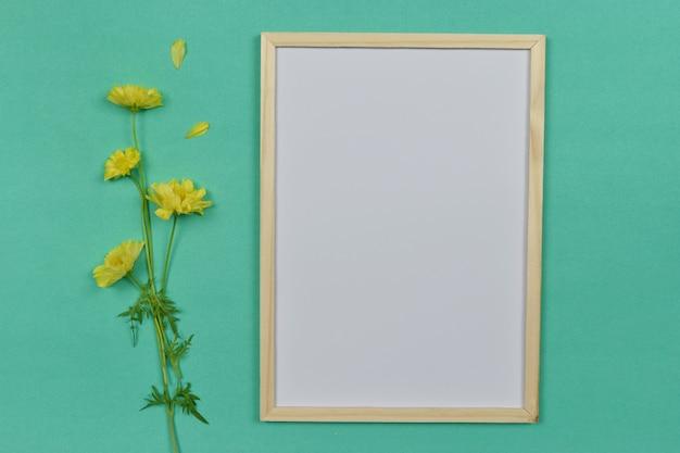 Пустая пустая рамка для фотографий с желтым цветком на стороне.