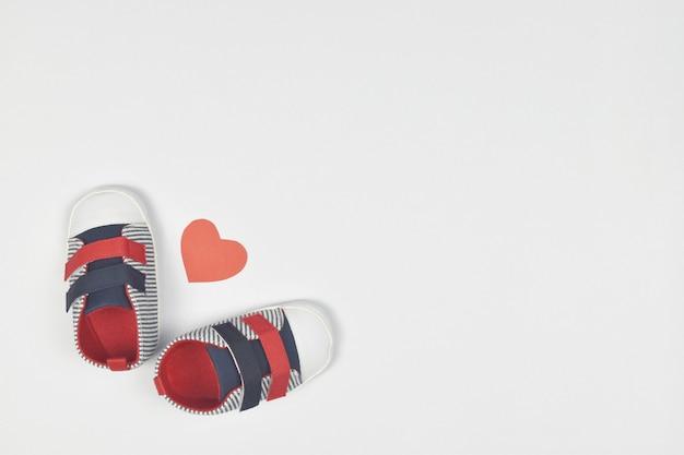 Детская обувь с красным сердцем формы на белом. копировать пространство.