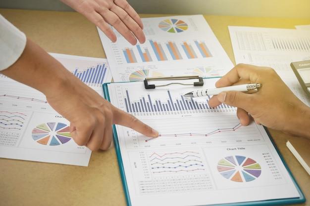 ビジネスの人々は、机の上の財務グラフとチャートを分析します。
