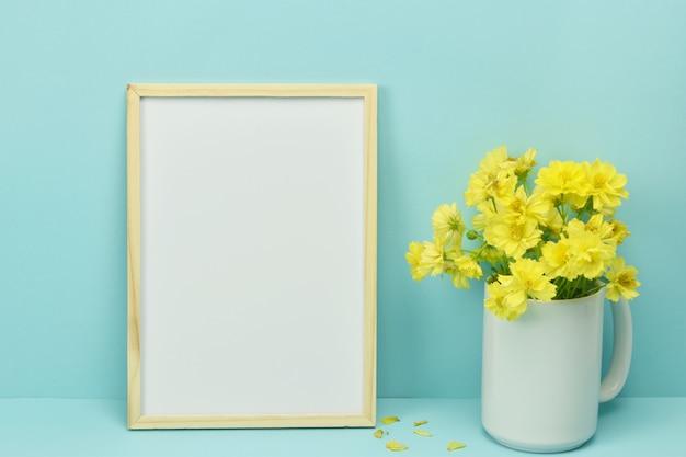 Рамка макет с желтыми цветами в вазе на синем.