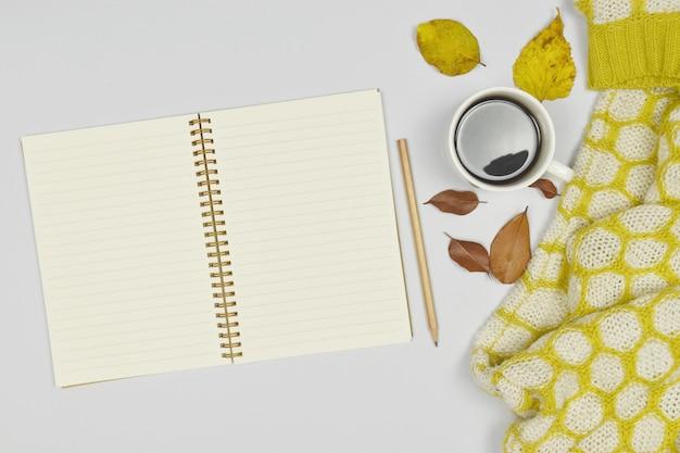 一杯のコーヒーとノートブックとセーターコート、白の紅葉