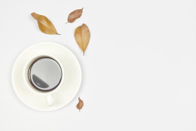 白地に秋の葉とコーヒーのカップ。コピースペース。