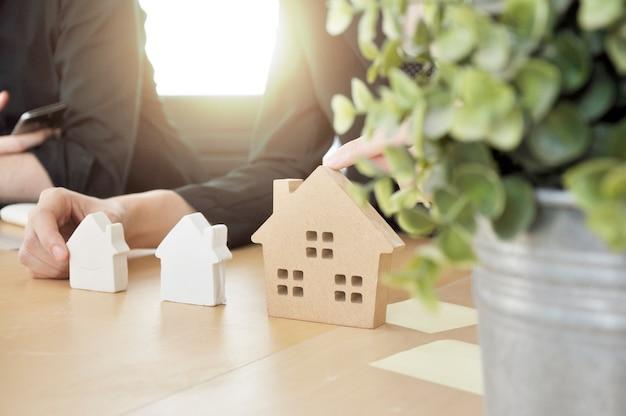 建築家のビルダーは、モックアップでテーブルの家を計画しています。