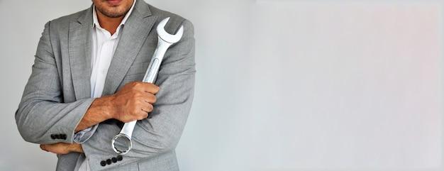 Человек держит гаечный ключ на сером фоне с копией пространства.