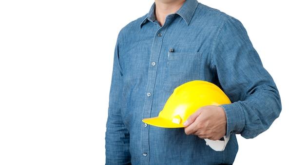 エンジニアワーカーは青いシャツを着て、分離の背景に黄色の安全ヘルメットを保持します。
