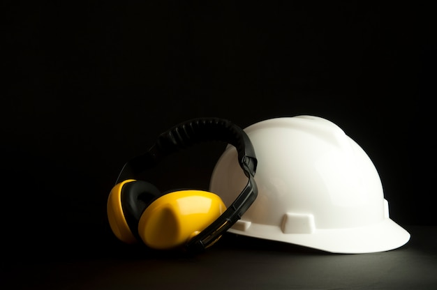 Безопасность наушников с белым защитным шлемом на черной предпосылке.