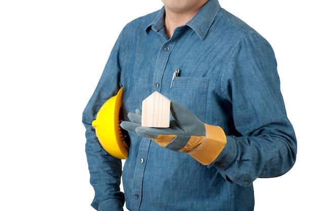 安全コンセプト建築家やエンジニアが青いシャツを着て黄色い安全ヘルメットを保持し、家のモックアップ