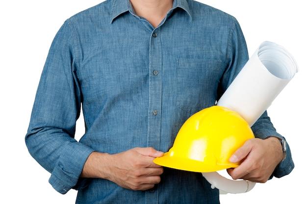 安全コンセプト建築は青いシャツを着て、黄色い安全ヘルメットとブループリントを保持します