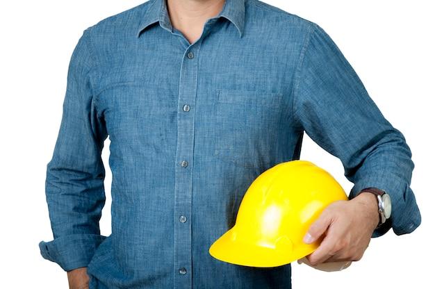 安全コンセプトエンジニアは青いシャツを着て、黄色い安全ヘルメットを握ります