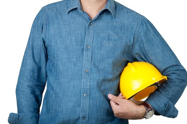 労働者は青いシャツを着て、分離の背景に黄色の安全ヘルメットを保持します。