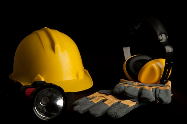 Желтый защитный шлем, кожаные перчатки, наушники, фара на черном фоне.
