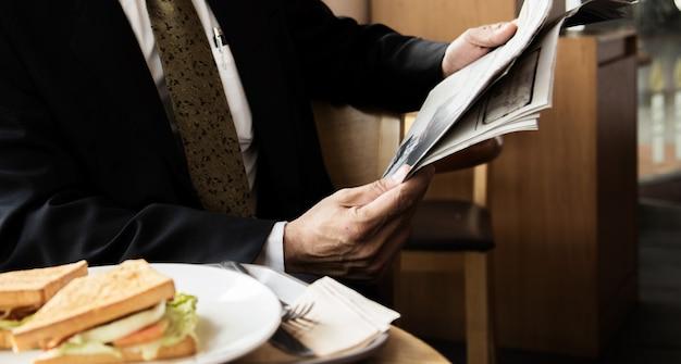 Молодой бизнесмен в черной куртке читает газету в кафе