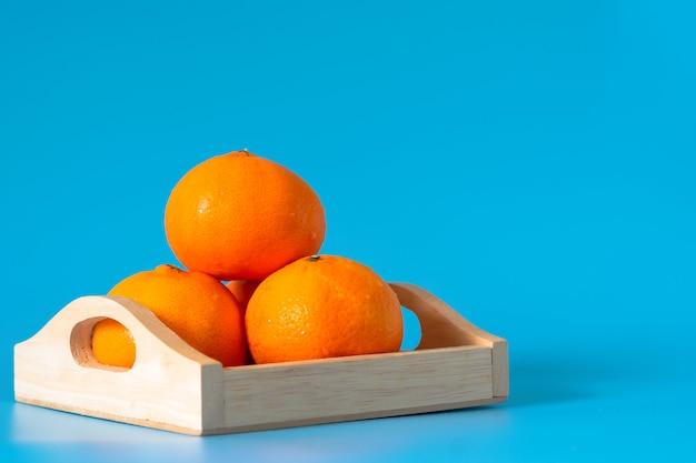 青の背景に木製の箱でオレンジ色の果物の夏。