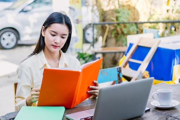Азиатские студенты. счастливая жизнерадостная молодая азиатская женщина усмехаясь и прочитанная книга в кафе