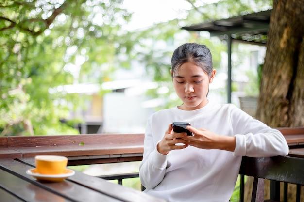 アジアの女性がコーヒーショップで携帯電話でメッセージを書くを使用して