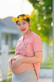 Азиатская беременная женщина в розовом халате и счастливо улыбается