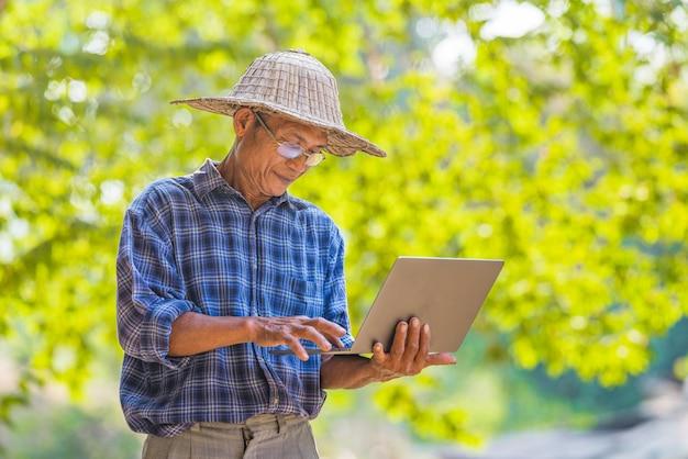 スマートフォンとラップトップのビジネスと技術の概念を持つアジア人農家、空のコピースペースのアジア人農家