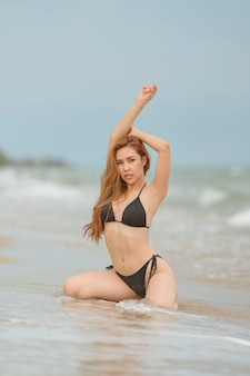美しいアジアの女性またはタイの女性とビーチで黒ビキニ、夏のコンセプトで旅行するためにビーチでリラックス