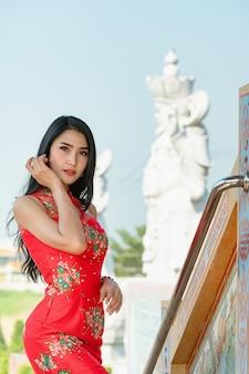 美しさの女性と中国の新年の買い物袋を保持
