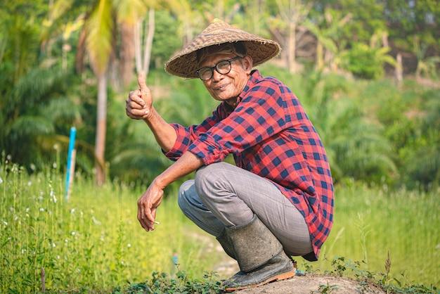 セサミガーデンで幸せな上級アジア農民の肖像画。