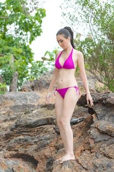 砂のビーチ、旅行屋外夏休みコンセプトでリラックスしたビキニで美しい若いアジア女性
