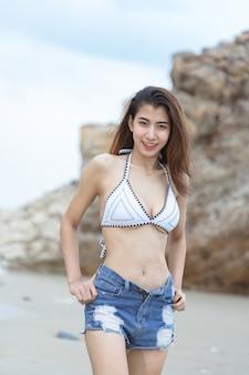 Красивая молодая азиатская женщина в бикини ослабляя на песчаном пляже, путешествует внешняя концепция летних каникулов