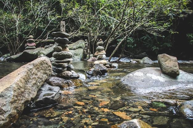 山の湖の滝の岸にバランスの取れた石ピラミッド。水面鏡の青い山。滝の照明条件。