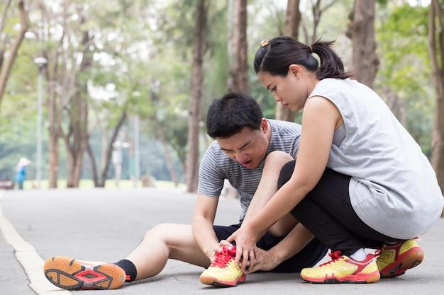 スポーツ傷害。ハムストリングの痛みと友人から助けを得る男