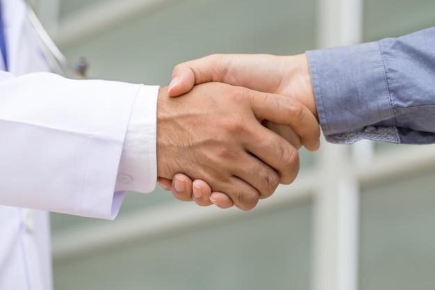 医者は患者と握手します。
