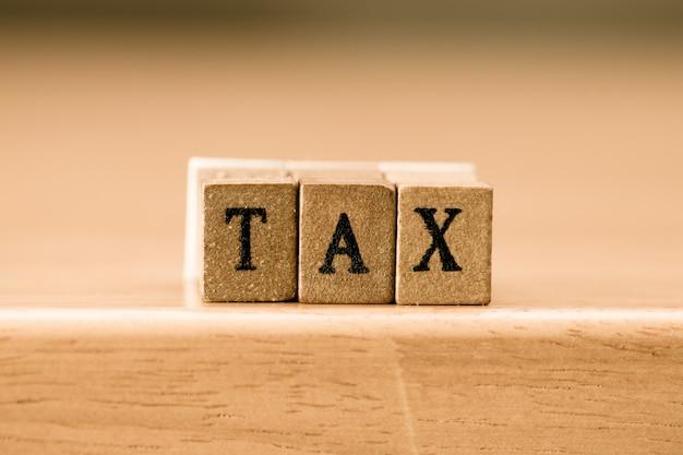 税金。ウッドブロック、ヴィンテージレトロな色調に書かれた言葉