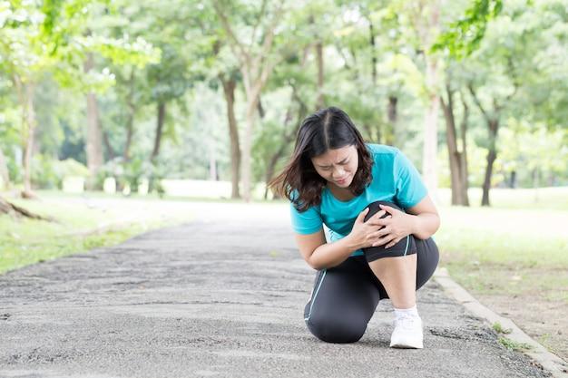 運動中の膝の痛みを持つアジアの若い女性